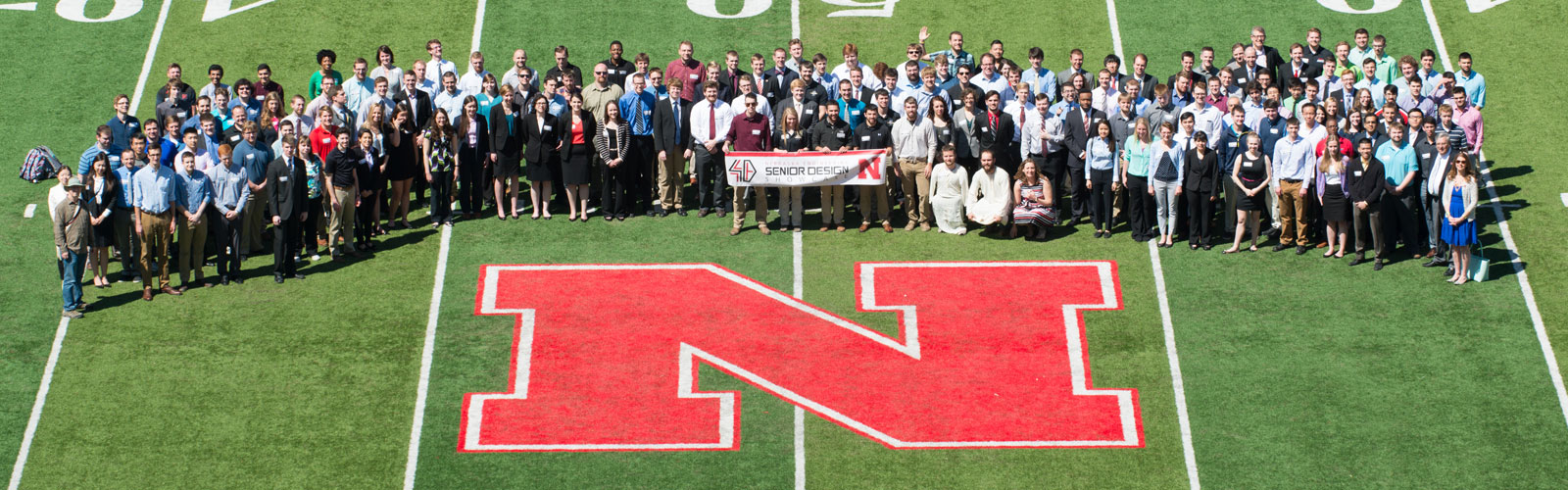 Senior Design Showcase participants take a photo at the 50-yard line of Memorial Stadium in Lincoln, Nebraska.