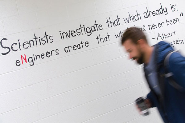 Student Walking in Hallway with Albert Einstein Quote Behind