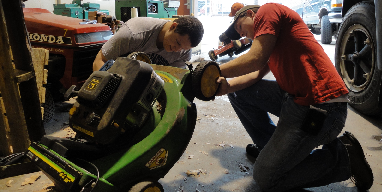 two AGEN students working with a lawn mower