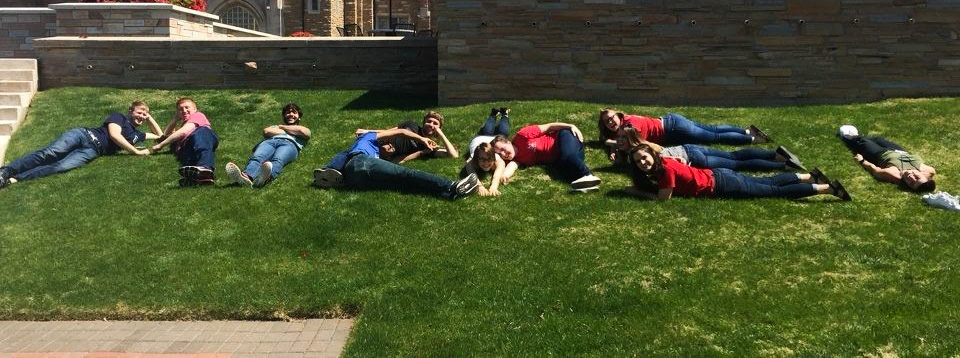Students laying in the grass outdoors using their bodies to write AIChE
