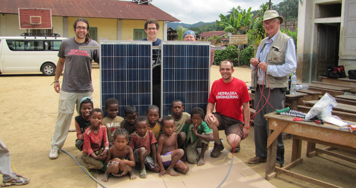 EWB members with children and solar panels in Madasgar.