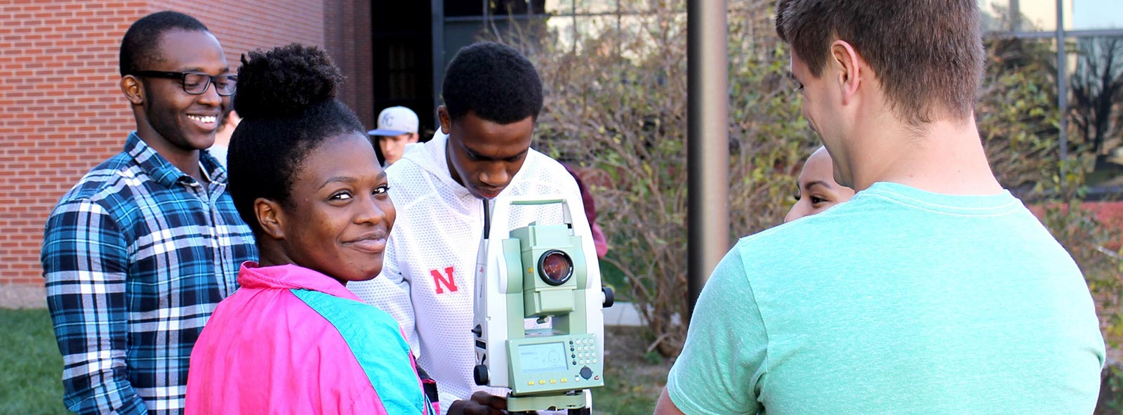 Four engineering students use a scope to survey outside the engineering complex. One student is facing the camera and smiling and another is looking into the scope.