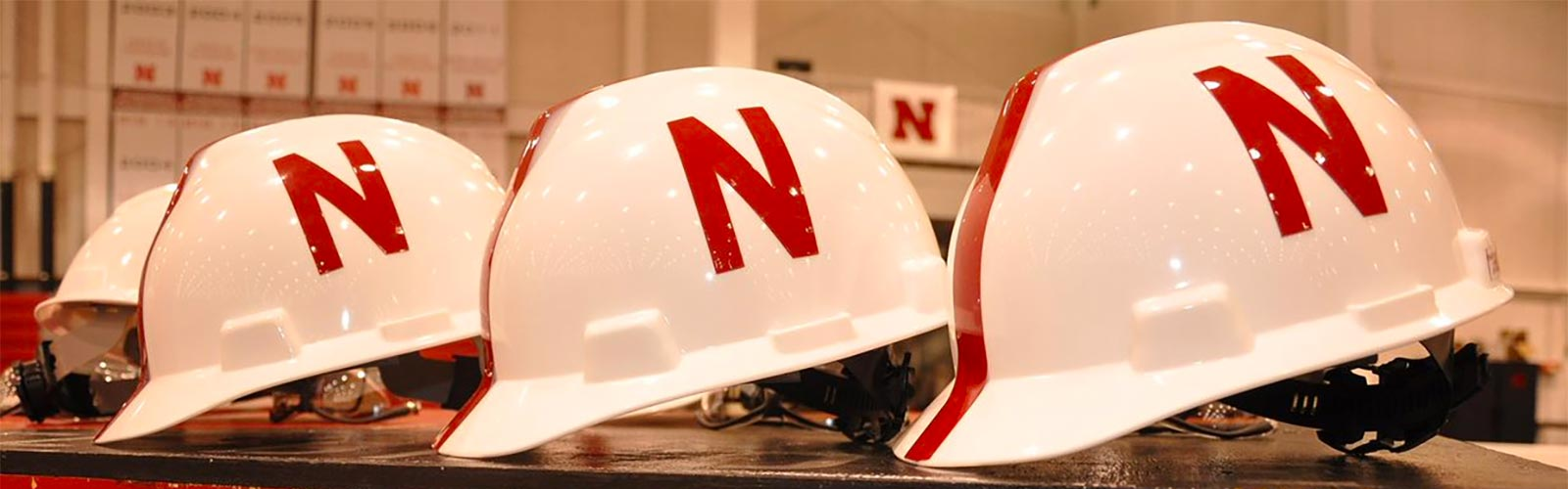 3 hard hats with Husker N's on them lined up next to each other.