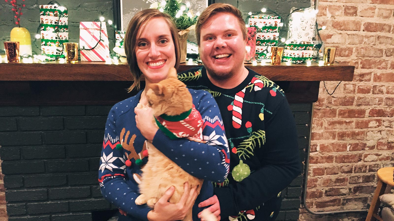 Jen and partner, Luke (he/him), posing with their orange tabby named Mango. She's pictured here not wanting to pose for a holiday photo.