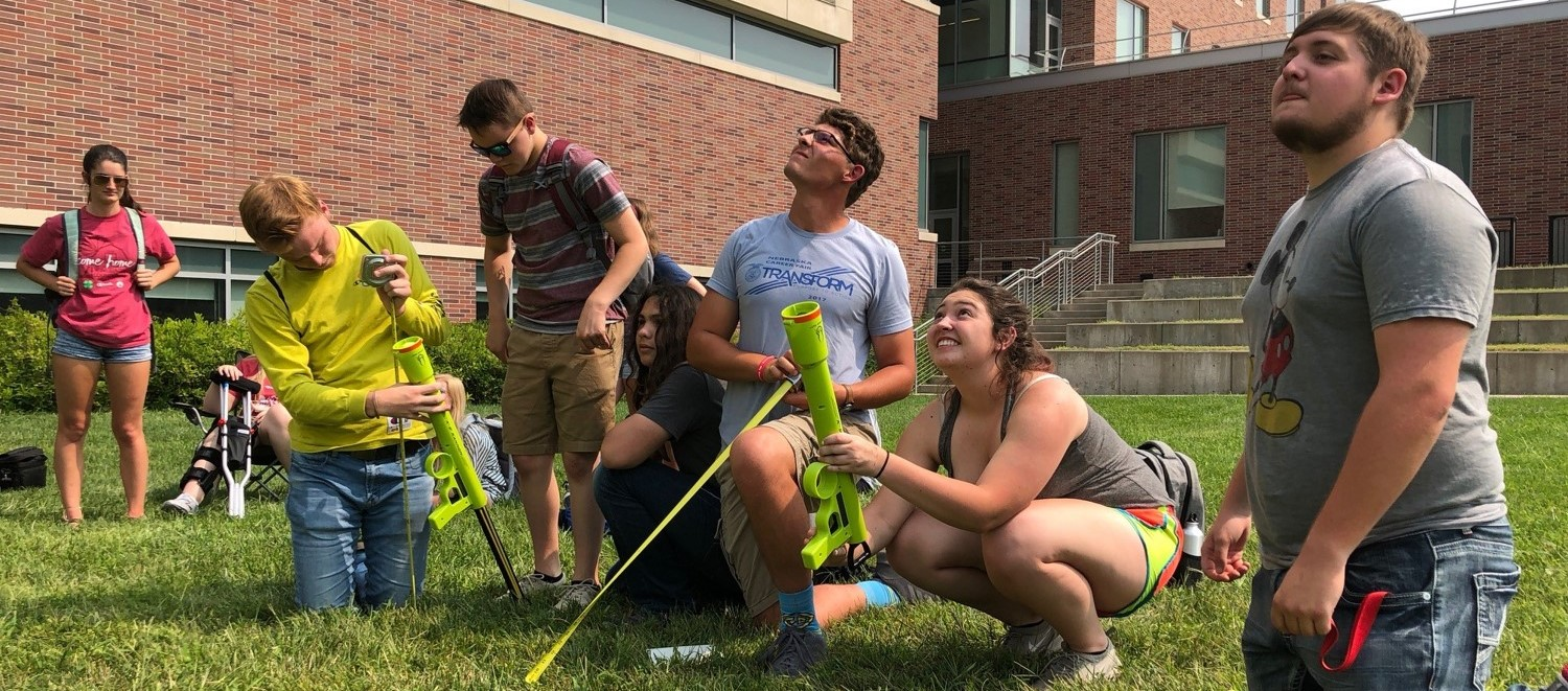 A group of engineering students observe as they launch a tennis ball into the sky with a launcher
