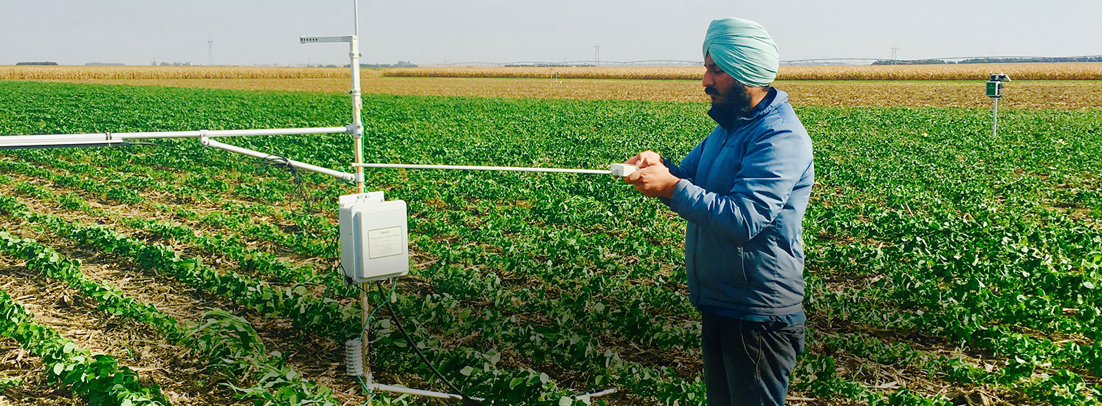 Meetpal Kukal standing in a farm field working with a device.
