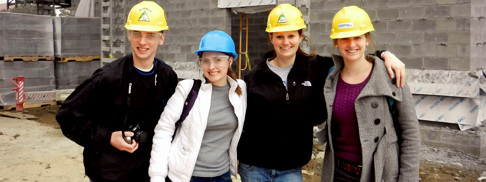 Students with hard hats standing in front of a work site