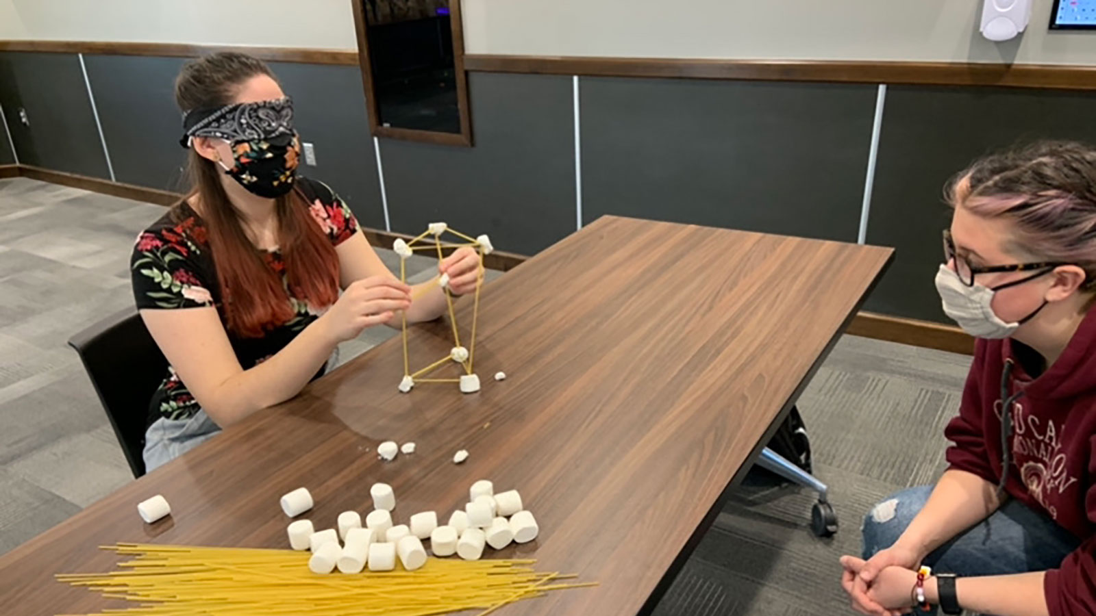 A team of 2 oSTEM members work together blindfolded to create a spaghetti tower building at a COVID-friendly event in 2020.