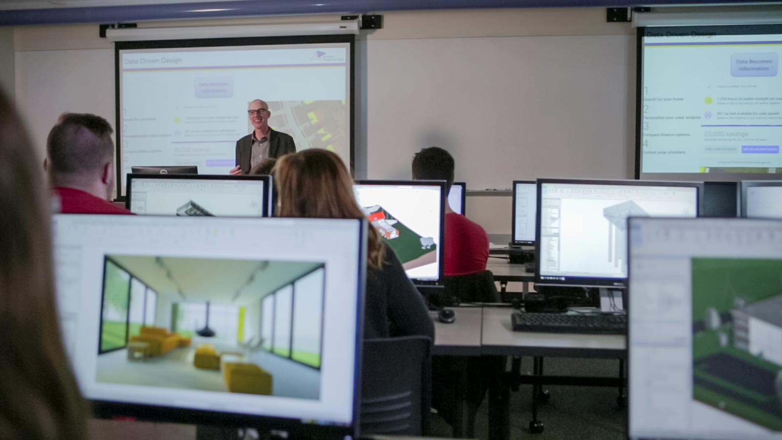 An instructor stands in front of a classroom with students sitting in front of computer screens.