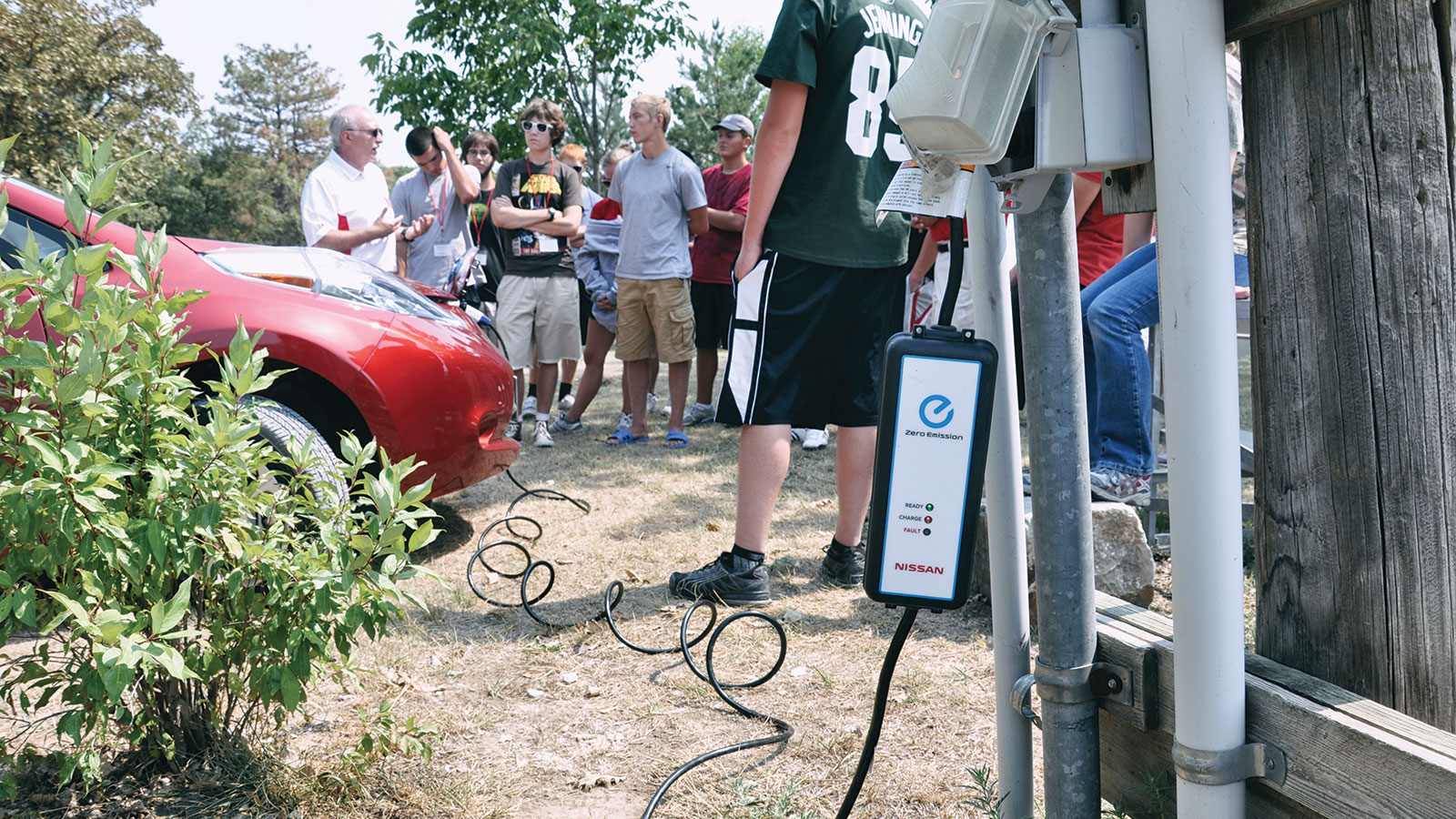 An electric vehicle is being charged as a professor talks with students.