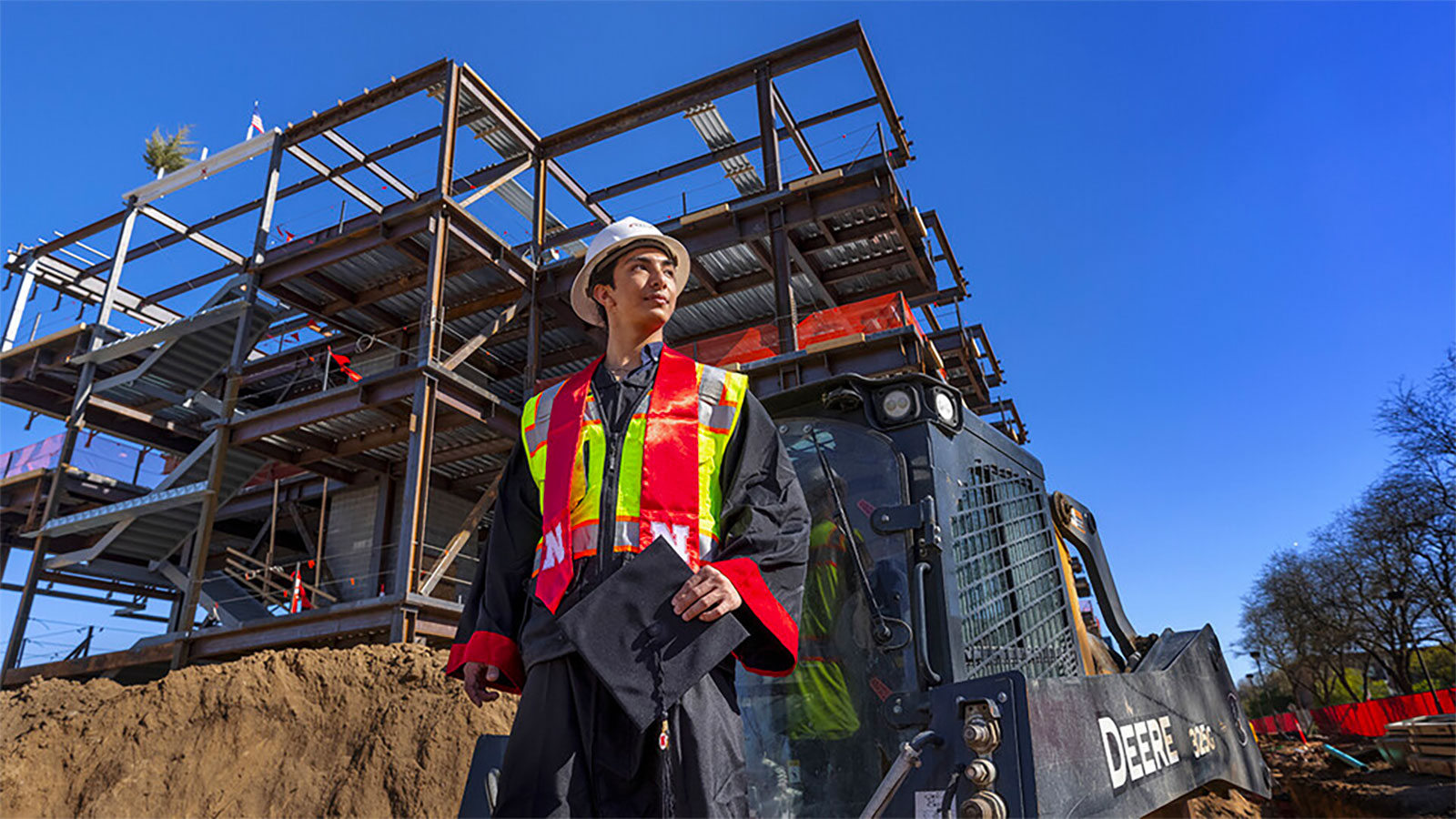 Yajyoo Shrestha, a graduating senior in civil engineering, stands before the construction site of the new College of Education and Human Sciences building on City Campus.