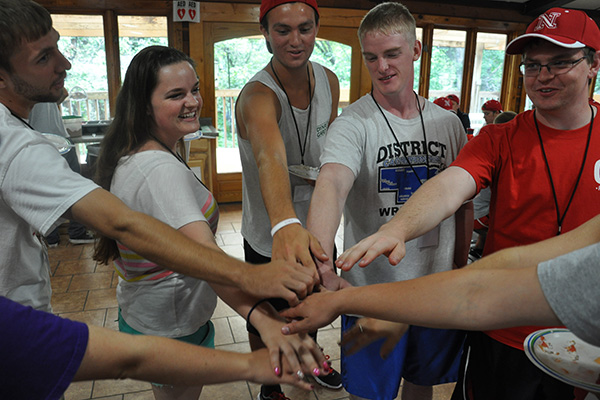 Students in a circle with hands today ready to do a high five