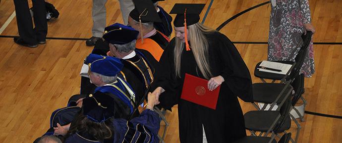 Graduate receiving handshake from facultymember