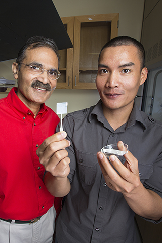 Ravi Saraf , Professor of Chemical and Biomolecular Engineering, left,  and post-doc Chieu Nguyen, holding up a thin membrane on a slide cover, have perfected a thin film which can detect small and deeply embedded cancerous tumors.