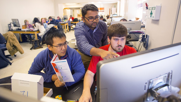 Santosh Pitla (center) assists students with a sensor-building project. Pitla is leading a new research project that will update techniques used to test tractors.
