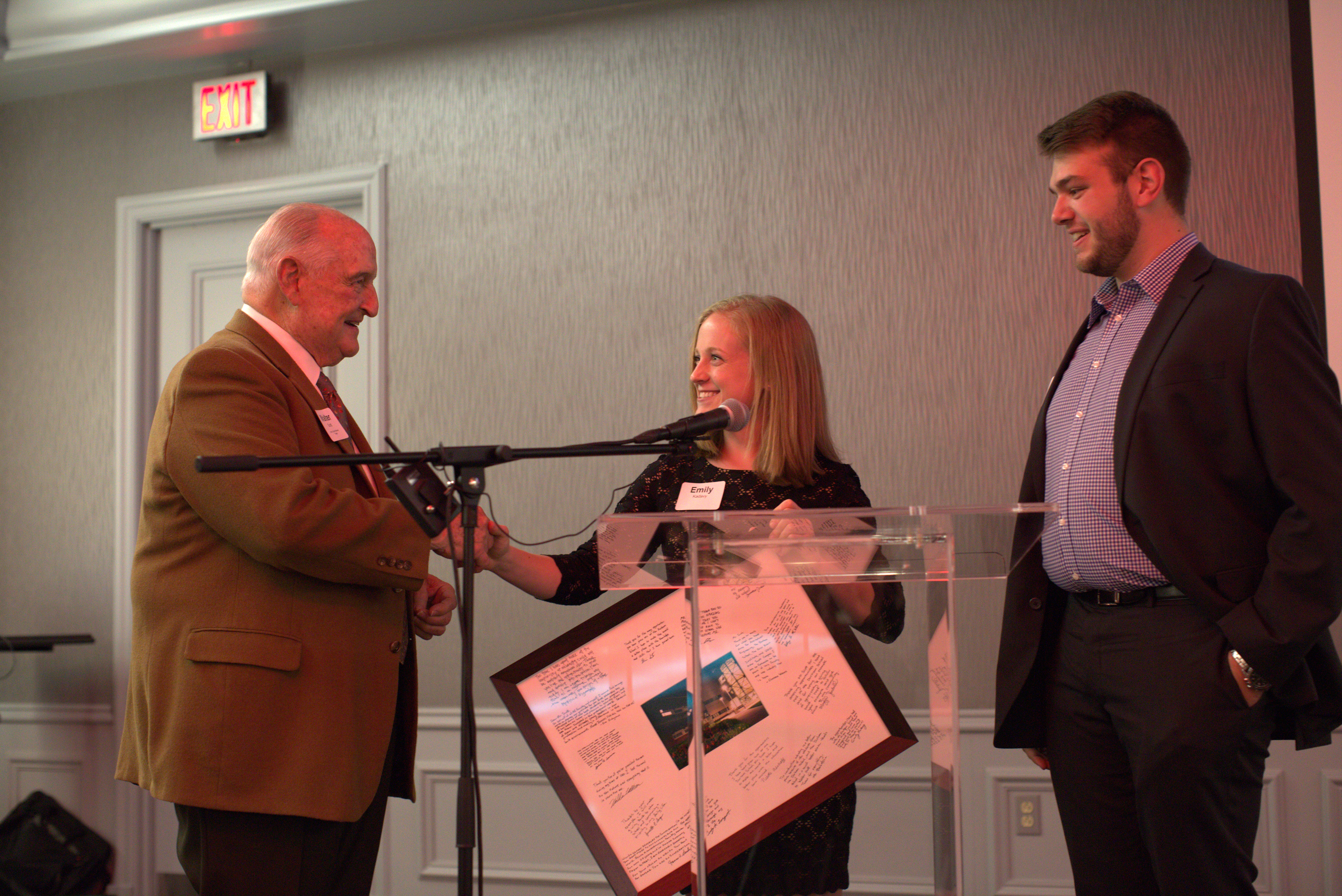 Walter Scott Jr. (pictured left) accepts a thank you memento from Scott Scholars Emily Kadavy (pictured middle) and Cody Largent (pictured right).
