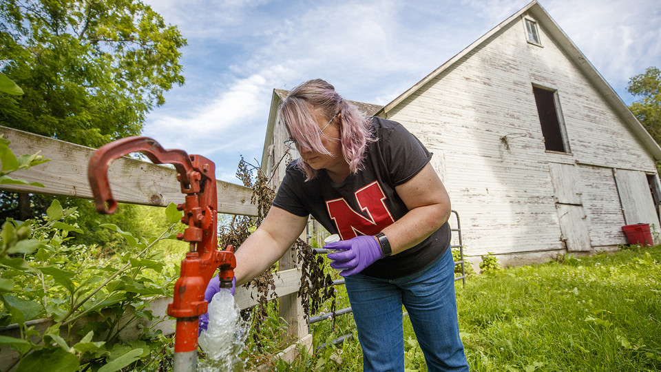 Jodi Sangster, a post-doc civil engineer specializing in environmental engineering, takes a water sample from a well spigot near Martell, Nebraska, July 1. (Craig Chandler / University Communication)