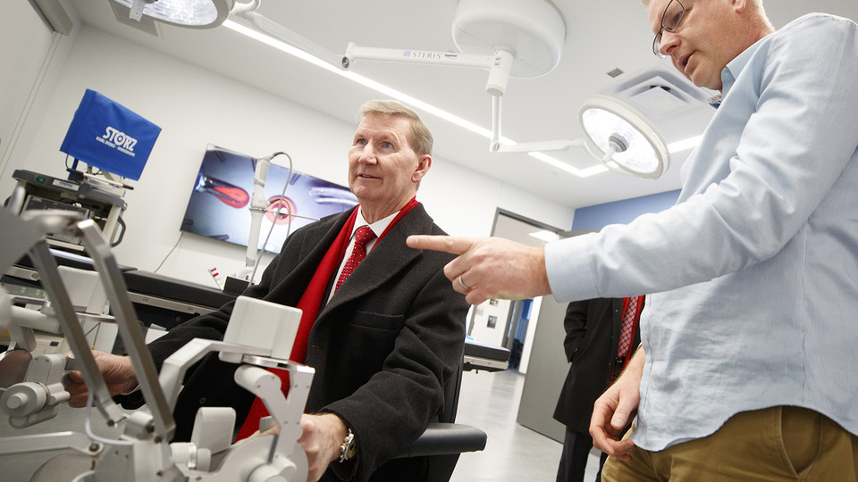Shane Farritor (right), professor of mechanical and materials engineering, helps University of Nebraska president Ted Carter control a surgical robot in a Virtual Incision lab at Nebraska Innovation Campus. (Craig Chandler / University Communication)