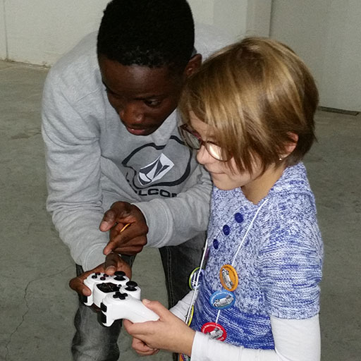 Daryl Dodoo, a junior computer engineering major, explains how to work the controls of a robot to 9-year-old Mia Vogel of Lincoln during the 2015 Nebraska Robotics Expo.