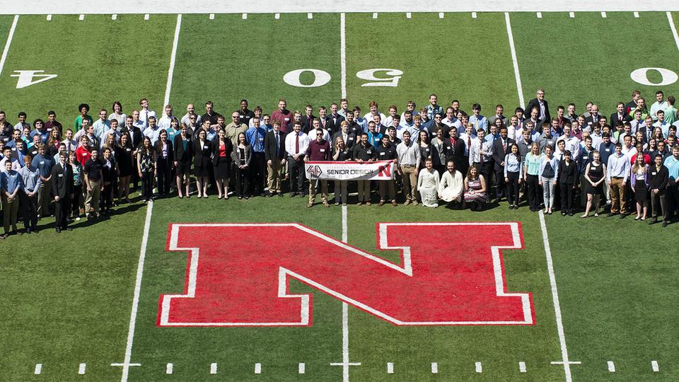 "2016 Senior Design Students pose around the 50 yard line ""N"" at Memorial Stadium."