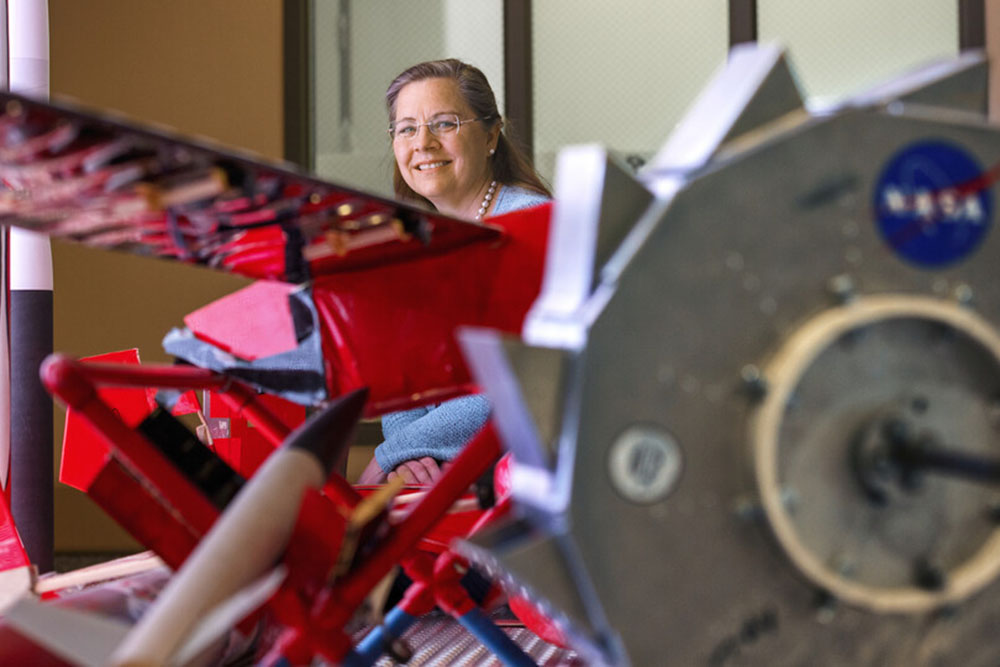 Karen Stelling is a professor of practice in mechanical and materials engineering. She is the adviser of the Aerospace Club, which is working on a satellite project with NASA, through a student grant project. She poses in the lobby of Othmer Hall with a display of Nebraska Engineering aerospace engineering projects. (Craig Chandler / University Communication)