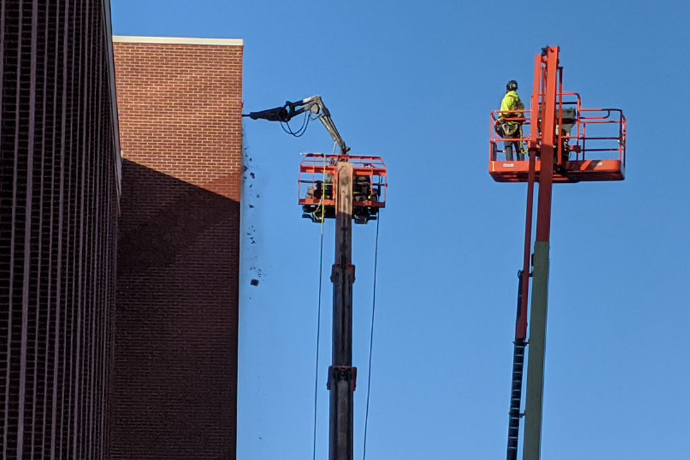 A robotic pneumatic jackhammer is used for demolition of a stairwell on the north side of Scott Engineering Center.