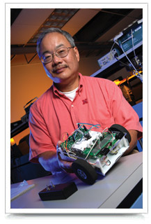 Dr. Bing Chen displays a TekBot.