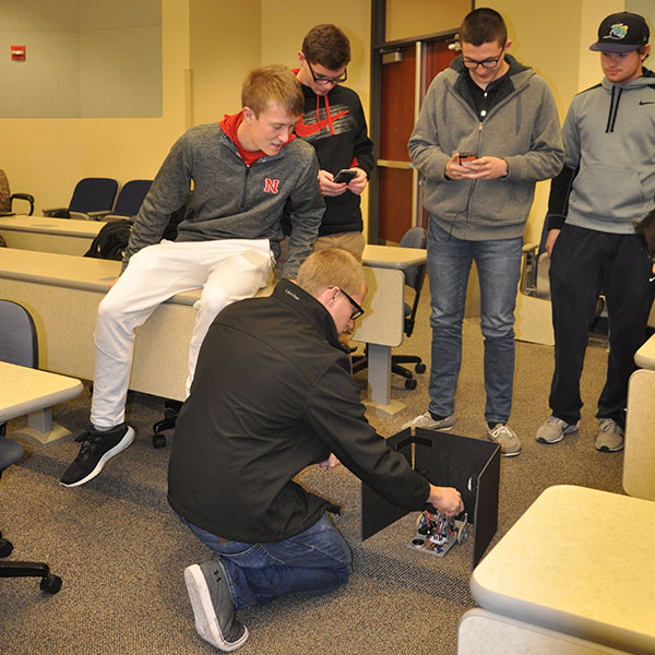 Students in ELEC 121 work on a device they created to shoot a rubber band from inside a three-sided box.