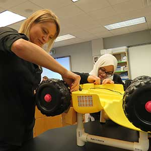 Hannah Jones (left) and Zainab Alsughayer work on the rear axle of an electric toy car that their team is working on as part of both their senior design capstone project and the Go Baby Go project.