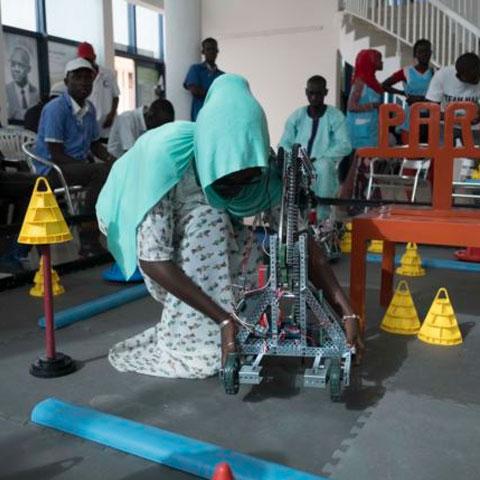 Marieme Toure, from Dakar, adjusts her team's robot at the 2017 Pan-African Robotics Competition in Dakar, Senegal, May 19, 2017. (R.Shryock/VOA)