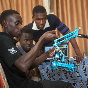 Sidy Ndao (left), associate professor of mechanical and materials engineering, examines a student team's assembled robot at the SenEcole robotics camp in Dakar, Senegal this past March.