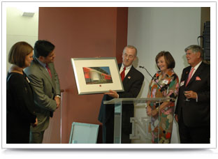 Chancellor Harvey Perlman (center) presents the Schorr family with a framed photo of the facility their gift made possible.