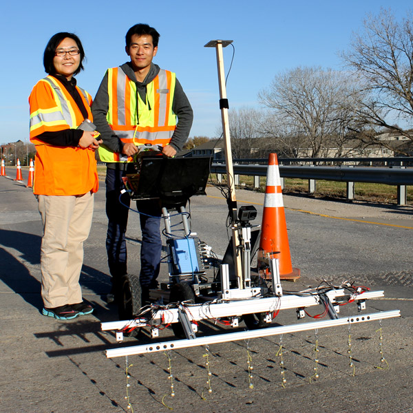 Dr. Jinying Zhu (left) with graduate student Hongbin Sun showing the cart rigged with the metal bead system.
