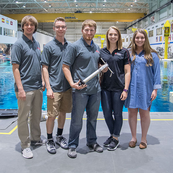 Nebraska Air and Space Research team members - (from left) Will Fleener, Nathan Borcyk, Andrew Mason, Allison Porter and Claire Ashley - demonstrated an anchoring device they designed at NASA's Johnson Space Center in Houston. The project was part of the annual NASA Micro-g NExT Challenge.