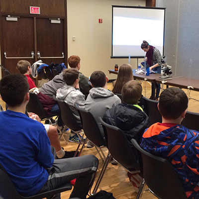 Rachel Levine, vice president of UNL's AWWA/WEF student chapter and a graduate student in civil engineering, shows middle school students an experiment during the Global Day of the Engineer, Feb. 24 at the Nebraska Union.