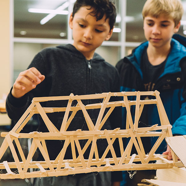 "Two students work on constructing a bridge during the ""Bridge Busters"" event."