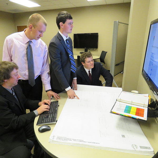 With Devron Crawford (left) at the keyboard, construction management capstone team members Alix Meisinger, Kelton Terry and Kyle Hohenstein go over their team's project schedule.