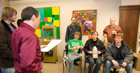 Steve Goddard (left), chair of computer science and engineering, reads a statement of good luck to members of the computer programming team that will compete in the Association for Computing Machinery International Collegiate Programming Contest. Team members include (back row) Jeff Ifland, assistant coach; and Charles Riedesel, coach of the team and assistant professor of practice. Photo by Greg Nathan/University Communications.
