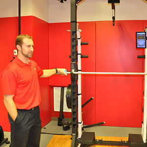 Curtis Tomasevicz, lecturer in electrical and computer engineering, shows a squat bar with sensors that are used to measure athletic performance in the Nebraska Athletic Performance Laboratory in Memorial Stadium. Tomasevicz, also a graduate student in biological systems engineering, is working at NAPL while doing doctoral research into how athletes create power while jumping vertically.