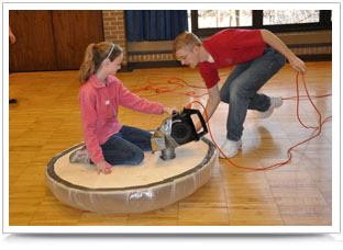 A middle school student rides on a hovercraft built by a UNL Engineering student.