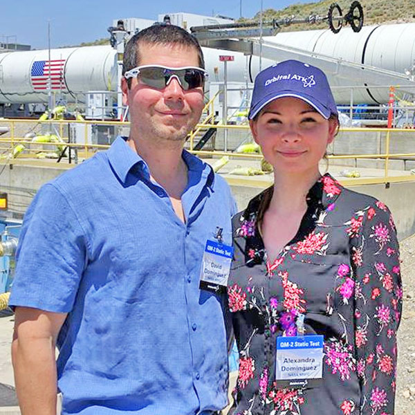 Alexandra Dominguez (right) and her husband, Dave, stand in front of a booster rocket at the Orbital ATK test facility in Promontory, Utah.