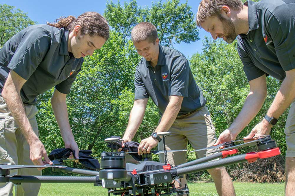 Evan Beachly (from left), Jim Higgins and Carrick Detweiler assemble a drone system before taking it for a test flight. The system features a software application that makes it easy to operate. It can also be flown at night, helping crews safely fight fires despite limited visibility. (Alyssa Amen / NUtech Ventures)