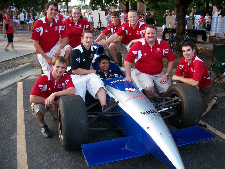 The UNL SAE team sits with their car.