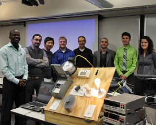 Members of Nebraska Engineering's I-SAVE team stand with their prototype energy monitoring device. From left to right are Evans Sordiashie, Hosen Hasna, Xueyi Wang, Tim Wisnieski, Mahmoud Alahmad, Wisam Nader, Sean Bergstedt and Caitlin Brow.