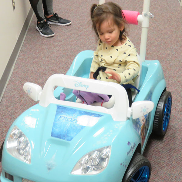 "Juliana Delgado pushes the button to make her ""Frozen""-themed car move for the first time during the Go Baby Go event Oct. 15 at UNMC's Student Life Center."