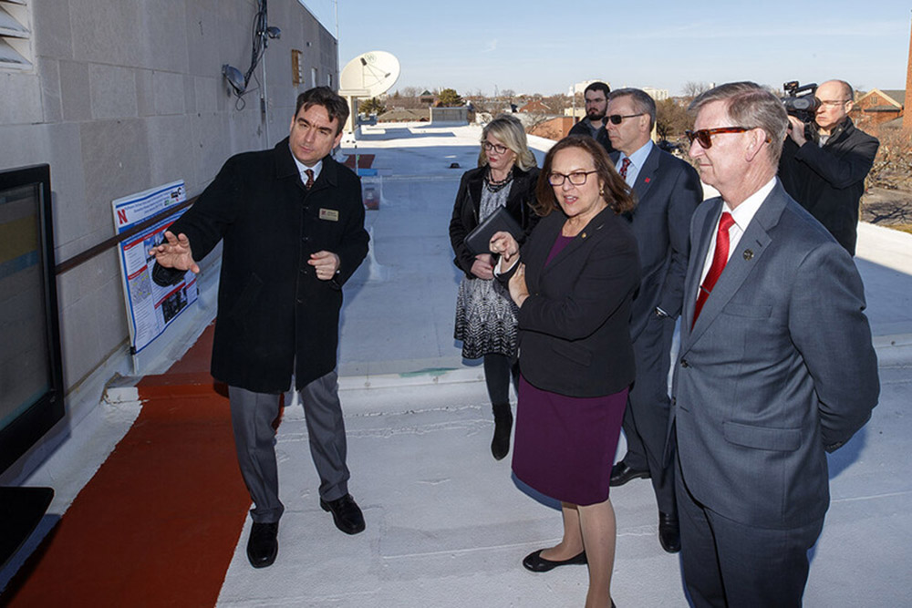 Atop Andersen Hall, Mehmet Can Vuran, Susan J. Rosowski Professor of computer science and engineering at Nebraska, briefs Sen. Deb Fischer, University of Nebraska President Ted Carter and University of Nebraska-Lincoln Chancellor Ronnie Green on wireless network research at the university.