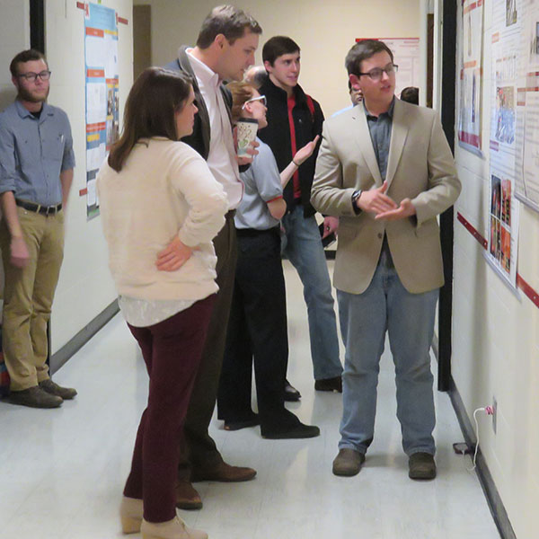 Undergraduate student Benjamin Bevans (right) discusses his research with assistant professor Michael Sealy during Friday's research fair.