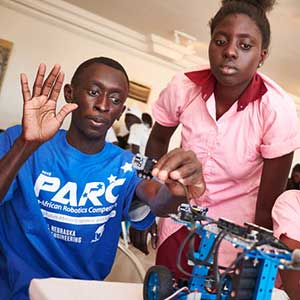 Sidy Ndao, assistant professor of mechanical and materials engineering, helps two students detect a problem on their robot during the Pan-African Robotics Competition. (Sam Phelps / New York Times)