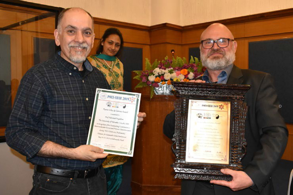 Mehrdad Negahban (left), professor of mechanical and materials engineering, received the Pierre-Gilles de Gennes Award for for Polymer Science and Technology at the International Polymer Characterization Forum (POLY-CHAR 2019) Conference in Nepal.
