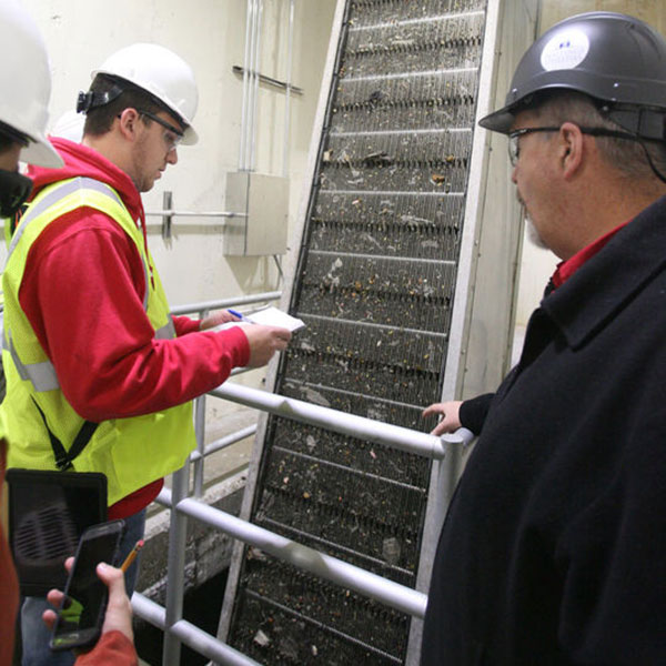 Brandon Schurman, a senior in mechanical and materials engineering, listens as site manager Jim Heyen (right) talks about the Grit Removal Unit building during a tour the Hastings Utilities Pollution Control Facility on Nov. 3. (Hastings Tribune photo)